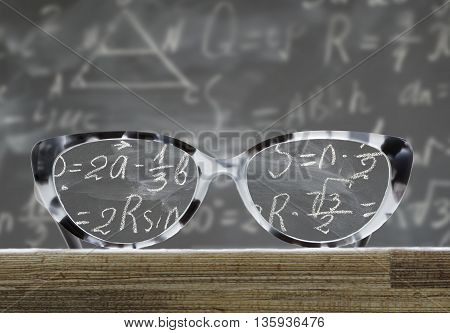 glasses on a wooden table in front of blackboard with math formulas, educational back to school concept