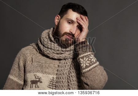 Close-up of young bearded man with headache over grey background