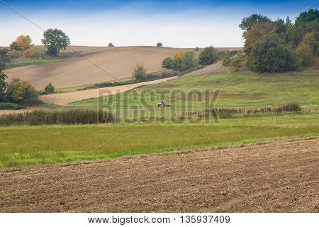 Farmer with agricultural tractor preparing the ground for crops