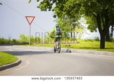 A Man On A Bicycle With A Backpack.