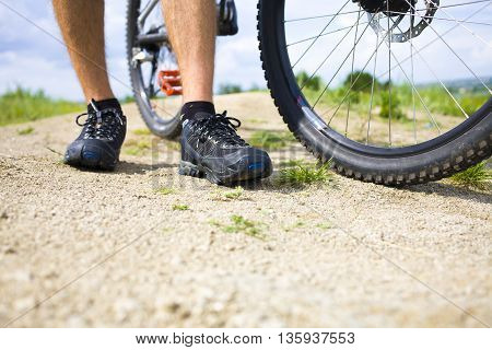 The Biker Stands Near His Bicycle.