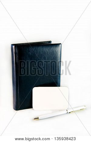 Leather dark diary and white pen near a blank card for writing