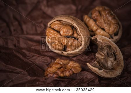 Close up cracked walnuts on brown paper