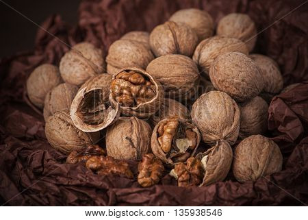 Cracked stack of walnuts on brown paper