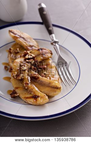 Grilled bananas for dessert wth nuts and caramel syrup