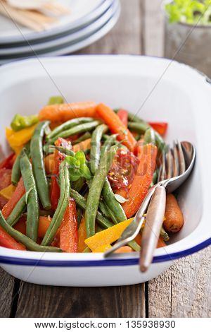 Grilled colorful vegetable side in a pan with green beans, carrots and bell peppers