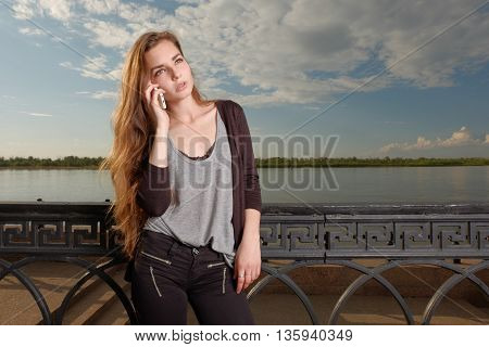 Pensive woman listening to the cell phone in front of waterfront fence and river surface