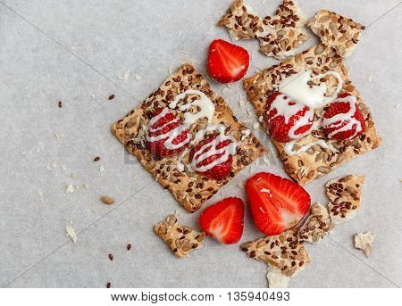 Red Fresh Strawberries are on the Cracker with Grains,Sweet Milk  on the White Paper.Breakfast Organic Healthy Tasty Food.Cooking Vitamins Ingredients.Summer Fruits.Top View