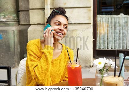 Smiling African Woman At Coffeeshop Making Phone Call
