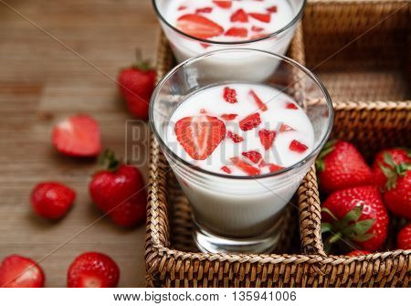 Two Glasses of Yogurt,Red Fresh Strawberries in the Rattan Box on the Wooden Table.Breakfast Organic Tasty Food.Cooking Vitamins Ingredients.Summer Fruits.