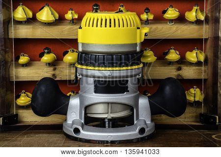 electric power router in front of wood cabinet full of assorted yellow metal router bits with wood background