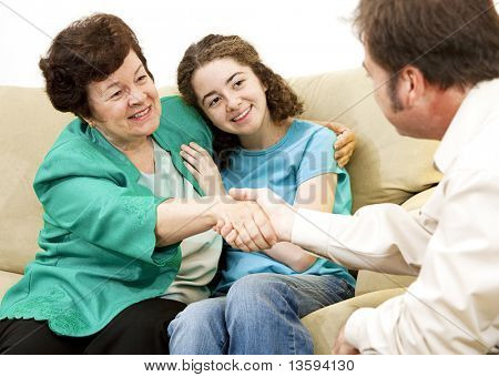 Mother and teen girl shake hands with a counselor.