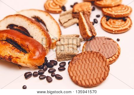 There are Pieces of  Roll with poppyseed,Cookies,Halavah,Chocolate Peas,Tasty Sweet Food on the White Background.Toned