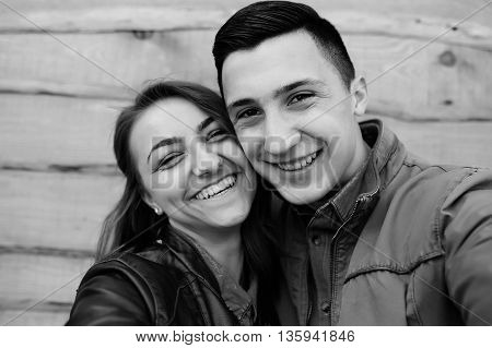 beautiful young couple posing on the background of wooden wall