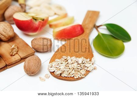 There are Banana,Apple,Orange with Walnuts in the Wooden Plate and Rolled Oats,Wooden Spoon,Trivet,with Green Leaves,Healthy Fresh Organic Food on the White Background,Selective Focus