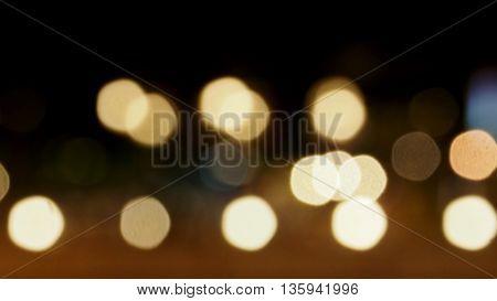 Bokeh blur warm white color on background black color are circle shape.