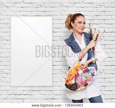 Happy artist. Woman with art tools. Female painter with brushes and palette. Empty easel with canvas at white brick wall with copy space. Art classes for adults, education concept.