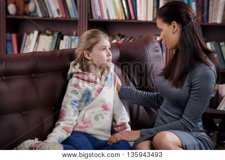 Child psychologist or mother talking with a little girl, a child is crying