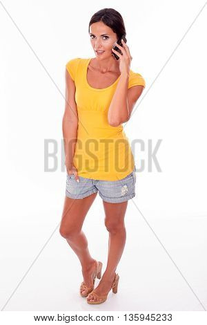 Thinking Brunette Holding A Cell Phone To Her Ear