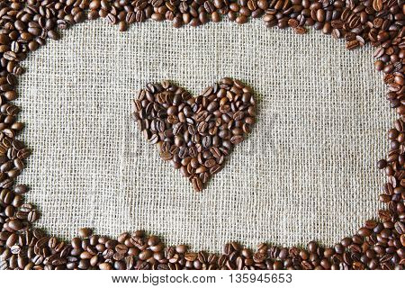 Burlap texture with coffee beans heart shape background, love symbol. Sack cloth canvas with copy space. Frame of seeds at hessian textile