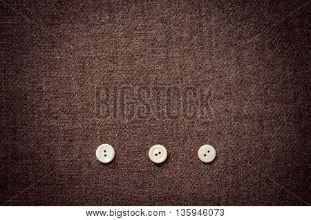 background of wool fabric and three buttons