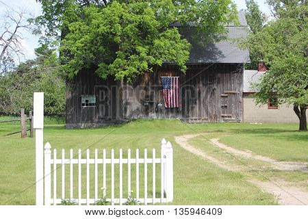 Old wooden barn with American flag white fence two track