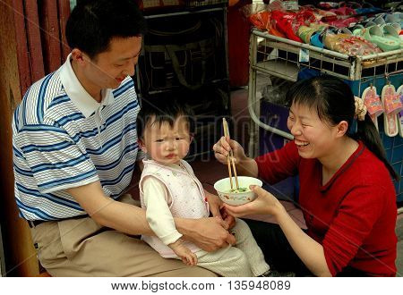 Dujiangyan China - April 24 2005: Mother feeding her toddler son who sits on his father's lap in front of their shop
