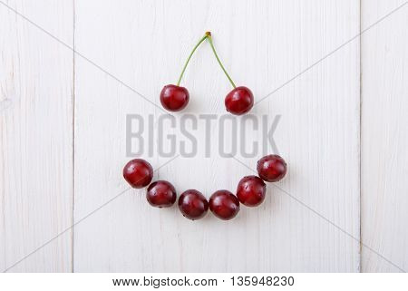 Smiley face from sweet fresh cherries. Smile sign from healthy food. Fruits closeup on white rustic wood pattern.