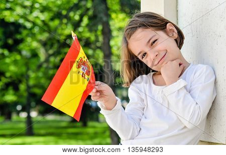 Portrait Of A Cheerful Young Girl With Spanish Flag
