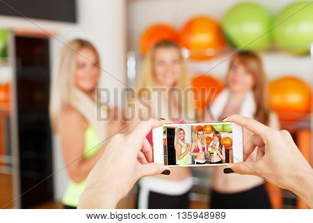 Taking photo of girlfriends. POV image of smartphone screen with girls after fitness training. Woman friendship, photographing and having fun. Portrait of smiling friends at mobile phone