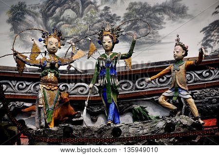 Dujiangyan China - October 9 2013: Hand-carved Chinese opera figures decorate the facade of the Ming Dynasty Nan Qiao covered bridge over the Min River