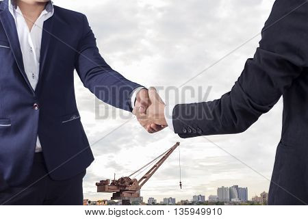 Two businessman shaking hands on factory background