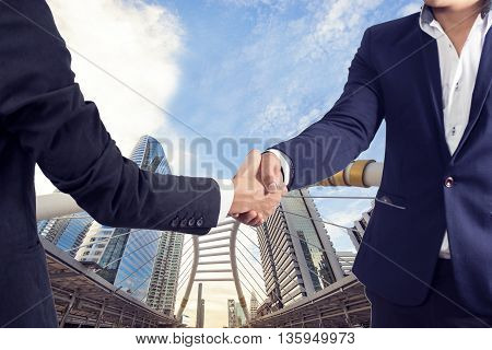 Two businessman shaking hands on modern city background