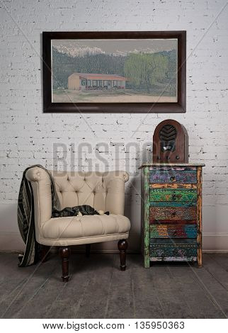 Composition of vintage beige armchair colorful cupboard aged wooden radio and hanged painting