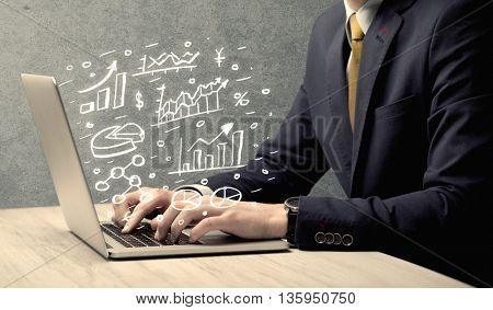 Sales person in suit using a laptop to calculate pie chart and exponential growth statistics on office desk concept