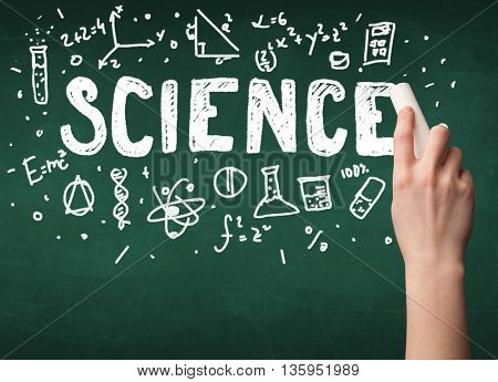 A teacher writing science, drawing chemistry elements on clean green chalkboard by hand