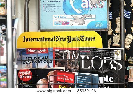 ATHENS GREECE - MAY 02; International newspapers headlines sold on news stand in Athens Greece - May 02 2015: Detail of kiosk selling internationals newspapers and magazines in Athens