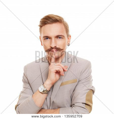 Young attractive man with mustache shows hush sign isolated at white. Handsome guy touch his lips with finger, secret ad mystery concept.