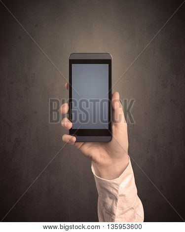 Caucasian hand in business suit holding a blank screen smartphone
