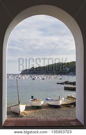 View trought the arch of the traditional fishing boats on the beach in Calella de Palafrugell Catalonia Spain