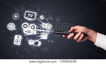 Hand holding a remote control, media icons coming out of it