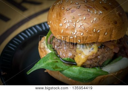 Detail on beef burger with cheddar (cheeseburger) with stronger vignette on black plate.
