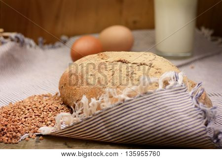 buckwheat bread glass of milk and eggs on a wooden table. Country Still Life. Vintage filterred photo