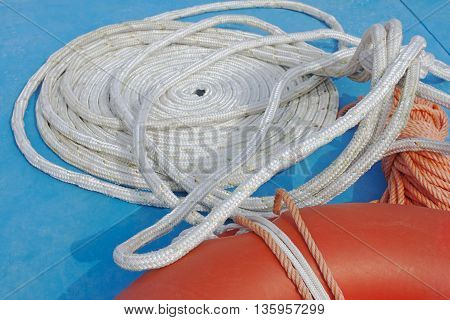 A folded spiral mooring rope with a circular orange buoy of rescue in the water