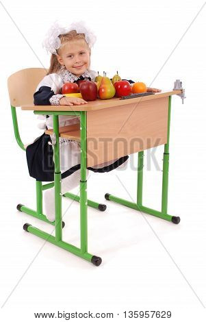 Little Schoolgirl sitting at a desk holding a lot of fruits white background with soft shadow
