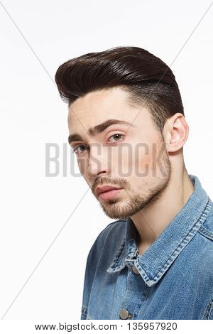 Portrait of handsome man in jeans shirt demonstrating modern hairstyle concept in studio. Male with bright black hair. Hairdressing concept. Studio shot.