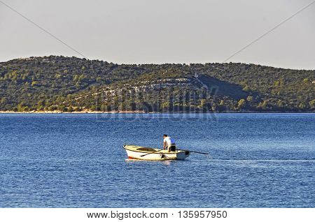 A young man practicing rowing in a traditional boat early in the morning facing away from the viewer