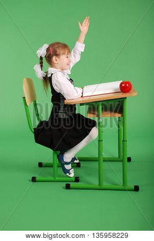 Girl in a school uniform sitting at a desk isolated on green background