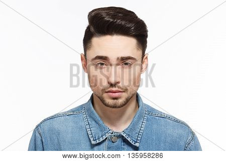 Portrait of handsome man in jeans shirtshowing his modern hairstyle isolated on white background. Male with short black hair in studio.