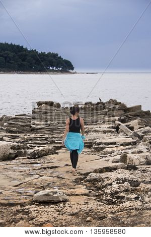 A young woman walking on rocks towards the tip of the rock formation